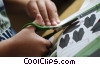 Stock photo  of a child cutting paper with
