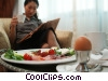 woman reading the newspaper after breakfast Stock photo