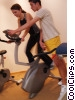 personal trainer and woman on stationary bike Stock photo